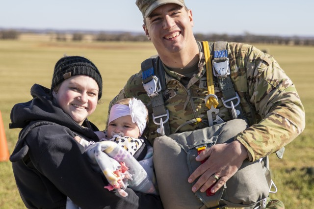 Sgt. Robert Hayduk, a petroleum supply specialist for Company I, 700th Brigade Support Battalion (Forward Support Company, 2-134th Infantry), smiles for a photo with his wife Heather and 8-month-old daughter while waiting for his turn on the helicopter. To officially signify the beginning of a new chapter in Nebraska Army National Guard history, the newly activated 2nd Battalion, 134th Infantry Regiment held a ceremony to unfurl company colors, Nov. 2, 2019, at the Husker Drop Zone near Yutan, Nebraska, followed by a airborne training exercise, where Soldiers parachuted from a CH-47 Chinook helicopter.