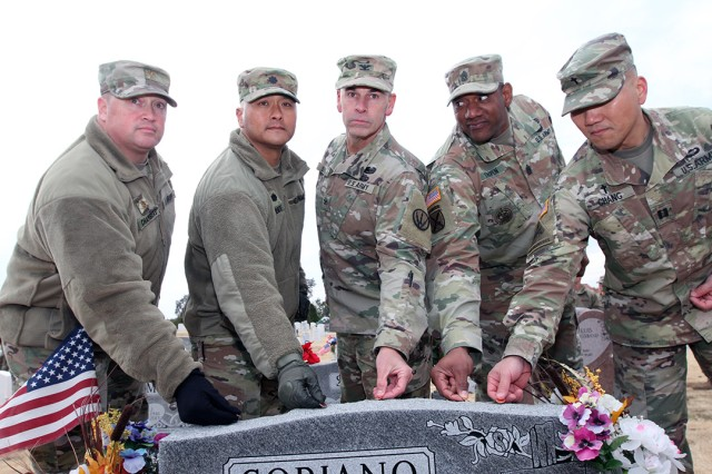 Leaders from 2-6th ADA place the first pennies on Air Force Master Sgt. Manuel Soriano's headstone Nov. 7, 2019, at the Fort Sill Post Cemetery to commemorate Veterans Day. From left, Maj. Christopher Chambers, executive officer; Lt. Col. Cedric Lee, battalion commander; Col. David Shank, Air Defense Artillery School assistant commandant; Command Sgt. Maj. Greg Thigpen; and Chaplain (Capt.) Jae Chang.