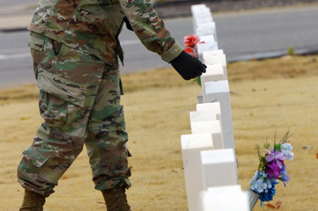 A 2-6th ADA Soldier puts one cent on top of a head marker Nov. 7, 2019, at the Fort Sill Post Cemetery. Virtually the entire battalion was there to commemorate Veterans Day.