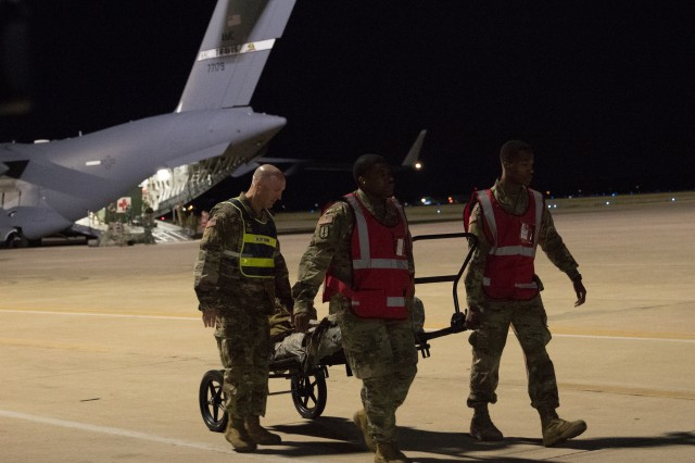 Soldiers offload a simulated casualty from an Air Mobility Command C-17 aircraft after arrival at Kelly Airfield as part of a U.S. Army Forces Command Emergency Deployment Readiness Exercise Nov. 4, 2019. The exercise tested Brooke Army Medical Center staff's ability to receive and provide definitive care to wartime trauma victims, as part of its Role IV wartime mission.