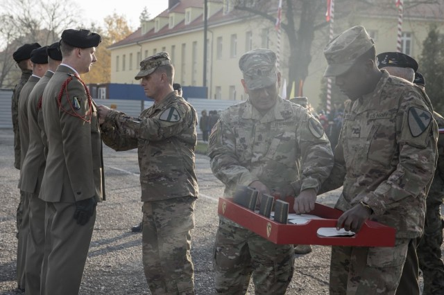 Col. Jeremy Wilson, commander of the 2nd Armored Brigade Combat Team, 1st Cavalry Division, and Command Sgt. Maj. Alexander Yazzi, command sergeant major of the 2 ABCT, 1st Cav. Div., presented four Polish Soldiers with the Army Achievement Medal on behalf of the U.S. Army during the 34th Armored Cavalry Brigade, 11th Armored Cavalry Division's Polish Independence Day Ceremony in Zagan, Poland, Nov. 8, 2019. (U.S. Army Photo by Maj. Stephanie Thomas)