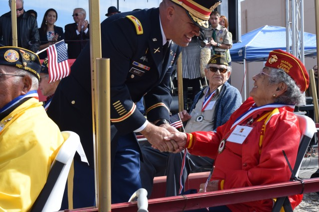 Col. Christopher Ward follows a salute to Marine Corps Veteran Carmen Ayers with a warm handshake.
