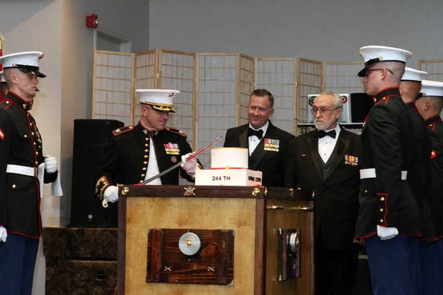 Fort Sill Marine Artillery Detachment Commander Col. Christopher Tavuchis cuts the birthday cake Nov. 9, 2019, at the Patriot Club. The first piece was presented to honored guest retired Lt. Col. Mike Grice (behind cake). The next piece was presented to the oldest Marine in attendance Sgt. James Lasswell (with beard), age 74. Lasswell served the third piece of cake to the youngest Marine Lance Cpl. Chontu Lee (far right, third from front), 20. The cake stand featured the Eagle, Globe and Anchor emblem superimposed on crossed cannons.