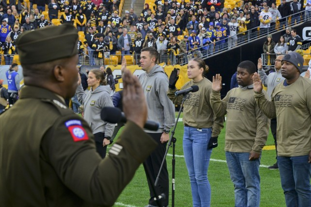 Lt. Gen. Bruce Crawford, the Army's chief information officer, administers the oath of enlistment with more than 60 future Soldiers, Sailors and Airmen during a mass joint-service swear-in ceremony at Heinz Field before the Pittsburgh Steelers vs. Los Angeles Rams football game, Nov. 10, 2019. The pre-game ceremonies were conducted in recognition of Veterans Day.