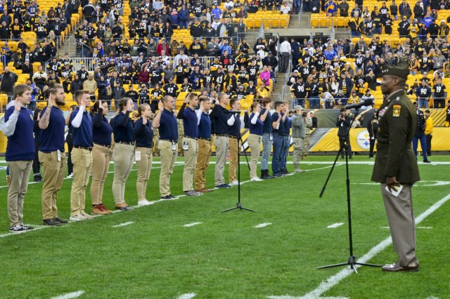 Lt. Gen. Bruce Crawford, the Army's chief information officer, administers the oath of enlistment with more than 60 future Soldiers, Sailors and Airmen during a mass joint-service swear in ceremony at Heinz Field before the Pittsburgh Steelers vs. Los Angeles Rams football game, Nov. 10, 2019. The pre-game ceremonies were in recognition of Veterans Day.