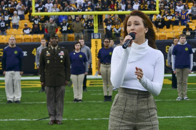 """Singer and songwriter Loren Allred, a Pittsburgh native, performs her hit single """"Never Enough"""" during a mass joint-service enlistment ceremony at Heinz Field as more than 60 future Soldiers, Sailors and Airmen who took the oath of enlistment in the pre-game ceremonies stand in formation behind her. Lt. Gen. Bruce Crawford, the Army's chief information officer, left, administered the oath of enlistment at the kickoff of the Pittsburgh Steelers vs. Los Angeles Rams football game, Nov. 10, 2019. The pre-game ceremonies were conducted in recognition of Veterans Day."""