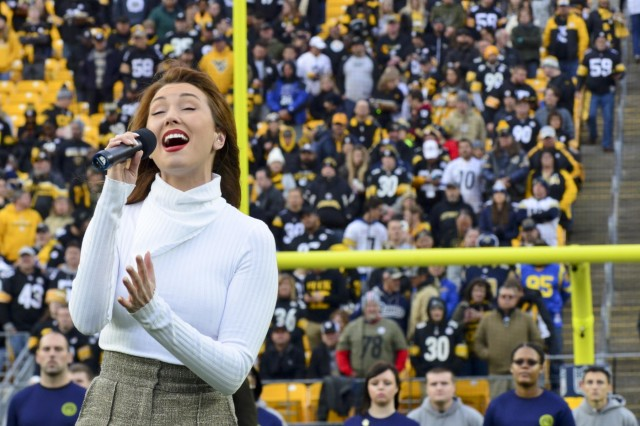 """Singer and songwriter Loren Allred, a Pittsburgh native, performs her hit single """"Never Enough"""" during a mass joint-service enlistment ceremony at Heinz Field. More than 60 future Soldiers, Sailors and Airmen took the oath of enlistment in the pre-game ceremonies of the Pittsburgh Steelers vs. Los Angeles Rams football game. The pre-game ceremonies were conducted Nov. 10, 2019, in recognition of Veterans Day."""
