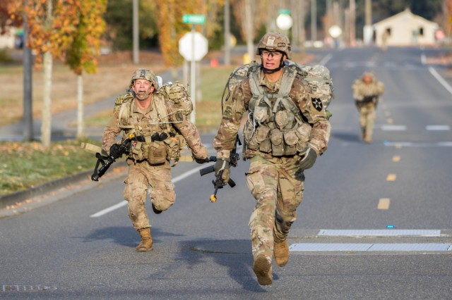 Soldiers race each other to the finish line of the 12-mile road march during 2nd Stryker Brigade Combat Team, 2nd Infantry Division's  Expert Infantry Badge and Expert Soldier Badge testing at Joint Base Lewis-McChord, Oct. 31, 2019. Both the EIB and ESB are designed to increase overall readiness and lethality on individual and unit levels across the Army, recognizing top soldiers who have met the highest standards of performance.