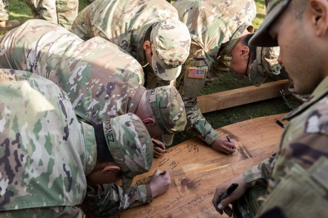"""Recipients of the Expert Infantry Badge and Expert Soldier Badge sign their names on an ESB and EIB hanging sign following 2nd Stryker Brigade Combat Team, 2nd Infantry Division's EIB and ESB award ceremony at Joint Base Lewis-McChord, Oct. 31, 2019. """"You've all accomplished something great,"""" said Brig. Gen. Timothy Leahy, deputy commanding officer for operations, 7th Infantry Division. """"You now bear the responsibility that comes with the EIB and ESB - the responsibility to pass on your expertise during training and the next EIB ESB event."""""""