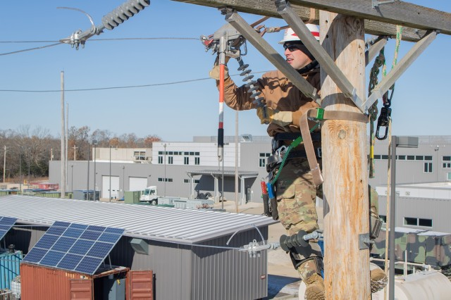 Sgt. Daniel Foote replaces a suspension insulator atop a 40-foot utility pole at the Lineman's Rodeo Nov. 12 at Fort Leonard Wood. Linemen wear rubber gloves to protect against energized lines.