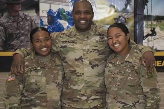 Chief Warrant Officer 5 Dean Registe, U.S. Army Engineer School Regimental Chief Warrant Officer, watched his daughters, Pvt. Malia Registe, left, and Pfc. Marlina Registe, graduate basic training at Fort Leonard Wood Nov. 14.