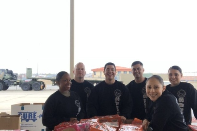 Staff Sgts. Tamika Wilcox, Daniel Kelly, Keli'l Torres, Fredrick Puff, Ashley McCurdy, and Miriam Reyes of the Fort Sill Chapter of the Sgt. Audie Murphy Club gather around a portion of the 10,200 pounds of food Fort Sill units donated Nov. 7, 2019, to the Lawton Food Bank.