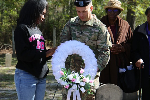 Lt. Col David Beavers, Installation Chaplain, helps Sanaya D. Frazier, age 16, place a wreath at the headstone of the church founder, Rev. Piner Martin. (Photo by Dina McKain)