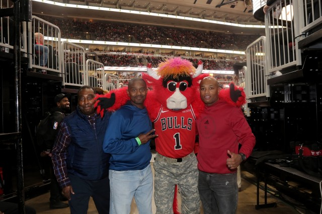 (From left to right) Chief Warrant Officer 3 William Brinston, Chief Warrant Officer 4 Tilmon Wooden, and Master Sgt. Laroy Warren pause for a photo with Benny the Bull, Chicago Bulls mascot, at a military appreciation game at the United Center in Chicago, November 9, 2019. (U.S. Army Reserve photo by Anthony L. Taylor)
