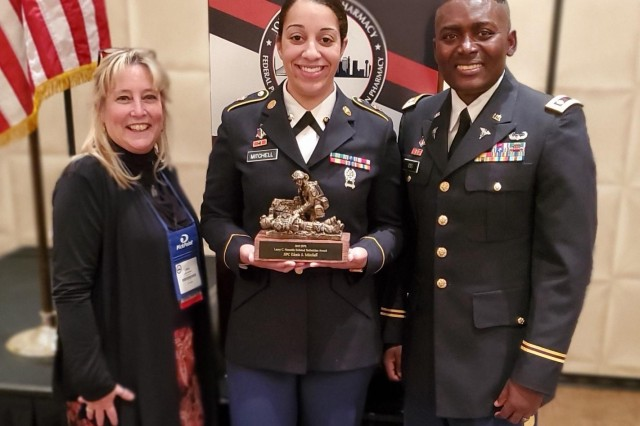 Spc. Elexis Mitchell, Kenner Army Health Clinic pharmacy technician, holds her Larry C. Nesmith Enlisted Technician Award she received Oct. 30, as Linda Hamilton, pharmacy supervisor, and Maj. Edward Osei, chief of Pharmacy, stand by her during the 2019 Joint Forces Pharmacy Seminar in Dallas, Texas.