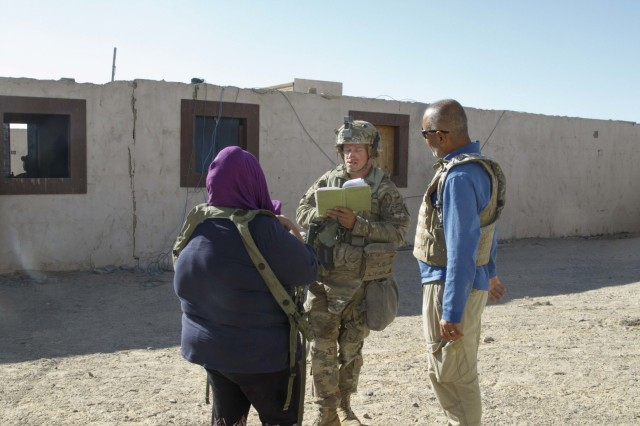 Sgt. Dawyne Darrow, a paralegal Non-commissioned officer with the Regimental Engineer Squadron, speaks with a citizen of Nabran Nov. 4, about a legal matter during a non-lethal stability training event at Fort Irwin, Calif. (U.S. Army photo by Maj. Marion Jo Nederhoed, 3rd Cavalry Regiment)