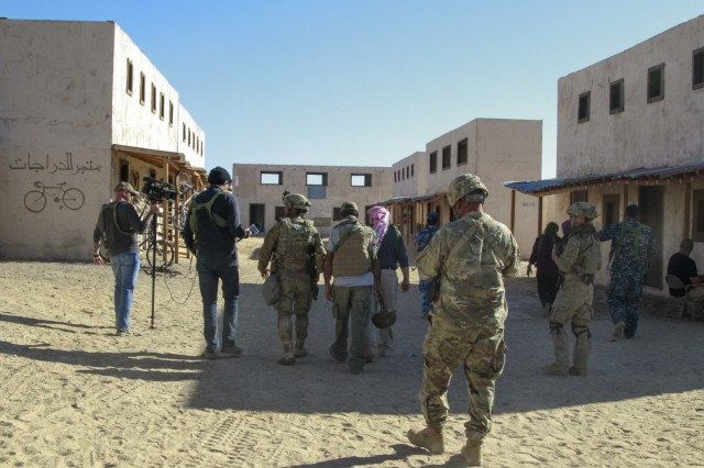 Civil stability assessment teams, media, police forces and Nabran leadership walk through the town to conduct an initial town assessment Nov. 4, during a non-lethal stability training even at Fort Irwin, Calif. (U.S. Army photo by Maj. Marion Jo Nederhoed, 3rd Cavalry Regiment)