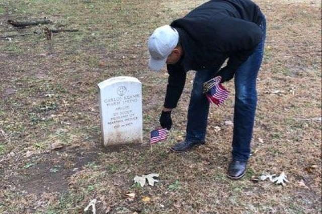 A Soldier assigned to 1st Battalion, 79th Field Artillery at Fort Sill, Okla., places an American flag at the grave of a service member. Battalion members took part in several functions throughout the week to honor veterans.