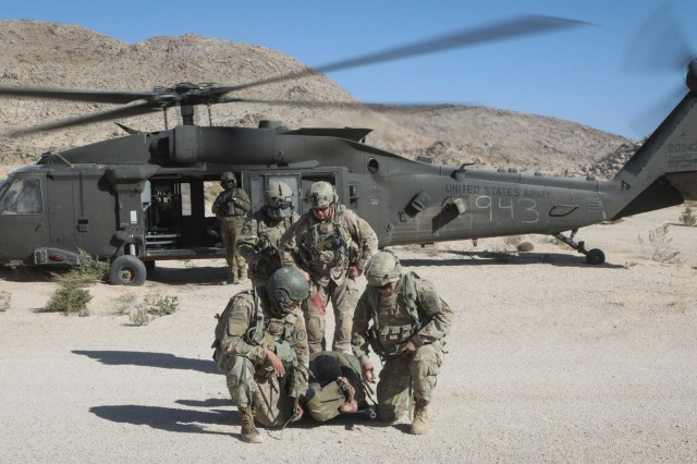 "U.S. Army Soldiers assigned to 3rd Cavalry Regiment ""Brave Rifles"", Fort Hood, TX, evacuate a simulated casualty in a UH-60 Blackhawk during Decisive Action Rotation 20-02 at the National Training Center in Fort Irwin, California, Nov. 1, 2019. Decisive Action Rotations at the National Training Center ensure Army Brigade Combat Teams remain versatile, responsive, and consistently available for current and future contingencies. (U.S. Army photo by Pfc. Brooke Davis, Operations Group, National Training Center.)"