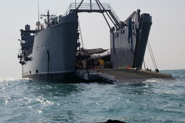 Members of the 511th Engineer Dive Detachment prepare to receive additional divers approaching from the front ramp of the U.S. Army Logistic Support Vessel 5 (LSV-5) near Kuwait Naval Base, Kuwait, Oct. 23, 2019. The vessel at the time was hosting joint training between U.S. Amy 511th Engineer Dive Detachment and members of the Kuwait Fire and rescue Service. (U.S. Army photo by Staff Sgt. Robert Waters)