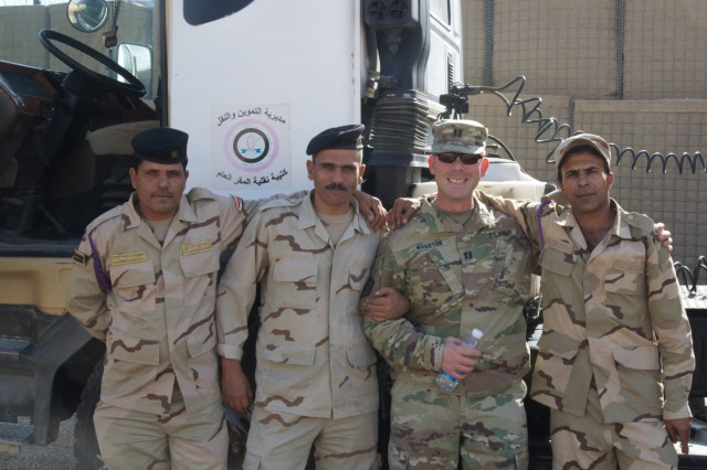 Soldiers from the Iraq Army Transportation Brigade pose for a photo with U.S. Army Capt. Richard E. Wharton,108th Sustainment Brigade, at Iraq's Joint Repair Parts Command, near Taji, Iraq, Oct. 23, 2019. The Iraqi Army has over 300 vehicle platforms they service to remain mission capable. (U.S. Army photo by Capt. Karla M. Crayne)