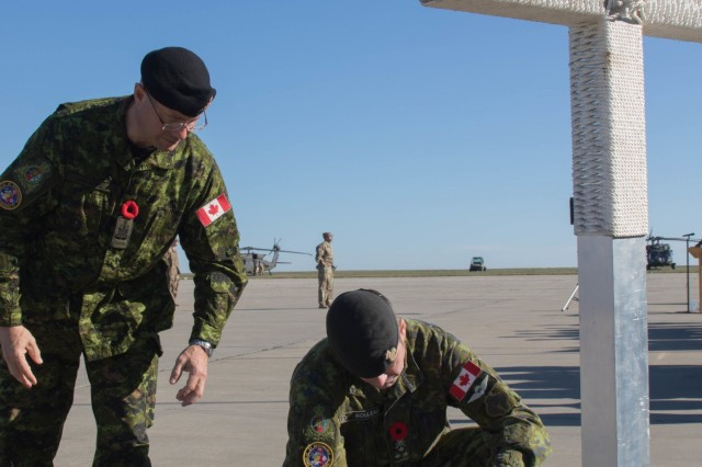 Chief Petty Officer 1st Class Gilles Grégoire, Canadian Joint Operations Command, and Lt. Gen. Michael Rouleau, CJOC commander,  lay a poppy-laden wreath in  front of a cenotaph cross as part of a Remembrance Day Ceremony held at Mihail Kogalniceanu Air Base, Romania, Nov. 11, 2019. Remembrance Day is a memorial day observed in Commonwealth member states recognizing the armed forces members who died in the line of duty during World War One.