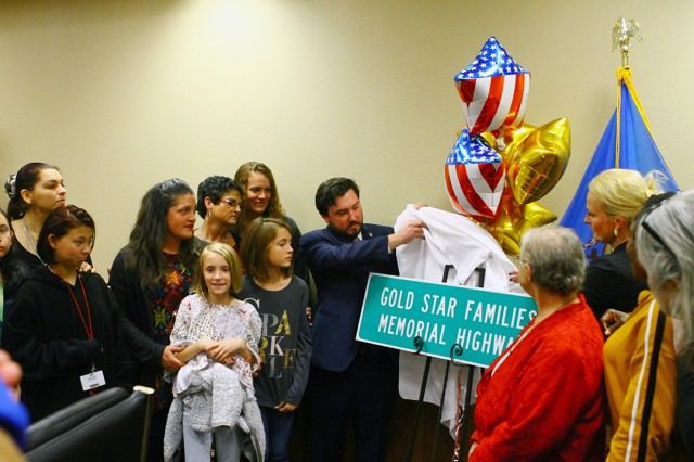 Oklahoma Sen. John Michael Montgomery and Rep. Toni Hasenbeck (blonde) unveil a replica of the Gold Star Families Memorial Highway Nov. 15, 2019, at the Lawton-Fort Sill Chamber of commerce. The sign on is U.S. 277 near the Fort Sill National Cemetery in Elgin, Oklahoma.