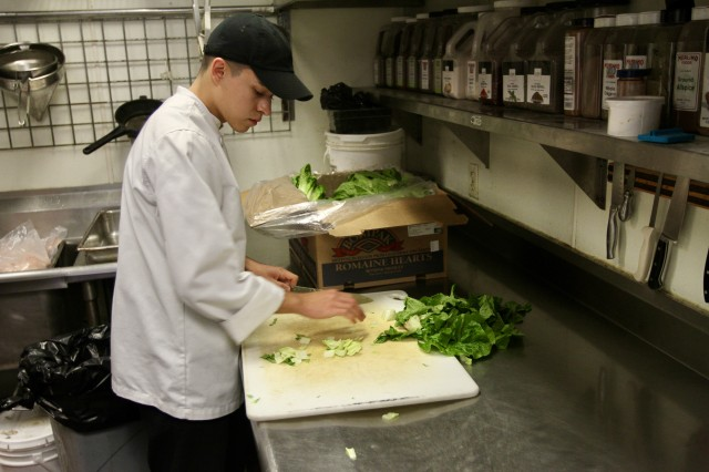 Pfc. Alexander Campos, a Sacramento, Calif. native, with 2nd Stryker Brigade Combat Team, 2nd Infantry Division, prepares lettuce before the lunch rush at Mercato Ristorante, in Olympia, Wash., Nov. 14, 2019. Representatives from Joint Base Lewis-McChord and the restaurant partnered together to broaden the opportunities and perspectives of the base's culinary specialists.