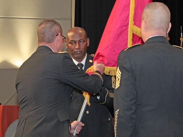 Maj. Gen. Mitchell hands the TACOM colors to Command Sgt. Maj. Charles