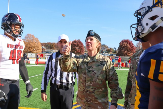 MURRAY STATE UNIVERSITY, Ky. - Col. Stephanie Barton, commander of the 101st Sustainment Brigade 'Lifeliners', 101st Airborne Division (Air Assault), flips a coin while Shaun Whittinghill (left), Austin Peay State University defensive lineman, Tyre Gray (right), Murray State University wide receiver and a referee look on during the military appreciation game at the Murray State University football field in Murray, Ky. on Nov. 16. (U.S. Army photo by Staff Sgt. Caitlyn Byrne, 101st Sustainment Brigade Public Affairs)