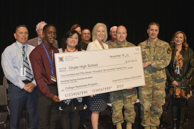 Holding the grant check from left to right is Jaymes George, Onate High School Student, Dr. Karen Trujillo, Las Cruces Public Schools Interim Superintendent, Shannon Manion, National Math and Science Initiatives Manager, Col. David Trybula, White Sands Missile Range Commander, Maj. Zachary Martin, White Sands Missile Range Operations Research Systems Analyst and other representatives at Oñate High School on Nov. 18. The U.S. Department of Defense, in conjunction with White Sands Missile Range and the National Math and Science Initiative, partnered to bring a college readiness grant to the school.