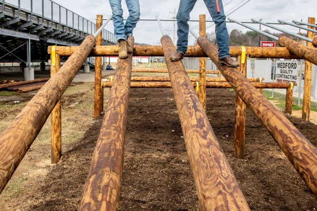 Two cadets from the Sissonville High School Marine Corps Junior Reserve Officer Training Corps (MCJROTC) demonstrate navigating an obstacle Nov. 19, 2019. Twelve engineers from the West Virginia Army National Guard completed the obstacle course project in one week as a part of an Innovative Readiness Training (IRT) program.