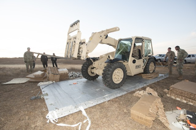 An operational Soldier places the Light Capability Rough Terrain Forklift 5K II into operation after being airdropped from U.S. Air Force C-17 cargo aircraft upon landing on Sicily Drop Zone, Fort Bragg, North Carolina. Test personnel conducted a technical inspection to ensure there were no damages upon impact.