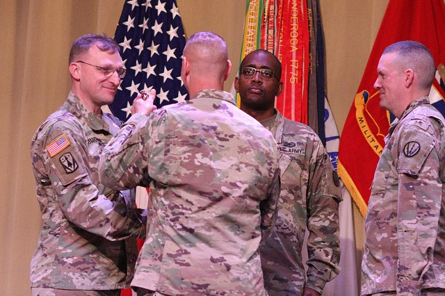 Col. Mark Holler, ADA School commandant and chief of ADA at Fort Sill, Okla., passes the officer saber to Chief Warrant Officer 5 Mitchell Brown signifying him as the chief warrant officer of ADA. Brown replaced retiring CW5 Eric Maule, right, during a change of responsibility ceremony Nov. 20, 2019, at Snow Hall.