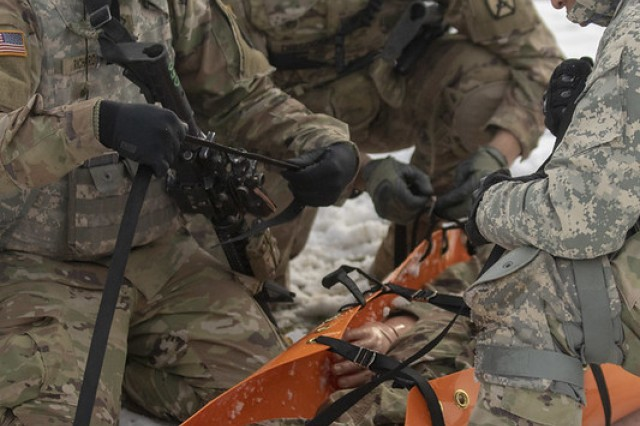 Pfc. Kevin Beeler, Spc. Aaron Drisdom, and Pfc. Kendall Richardson, all of Headquarters Support Company, Headquarters and Headquarters Battalion, 10th Mountain Division (LI), adjust the straps on a Skedco before transporting a casualty Nov. 18, 2019 on Fort Drum, N.Y. HHBN conducted bunker live fires and response to casualties Nov. 18-19.