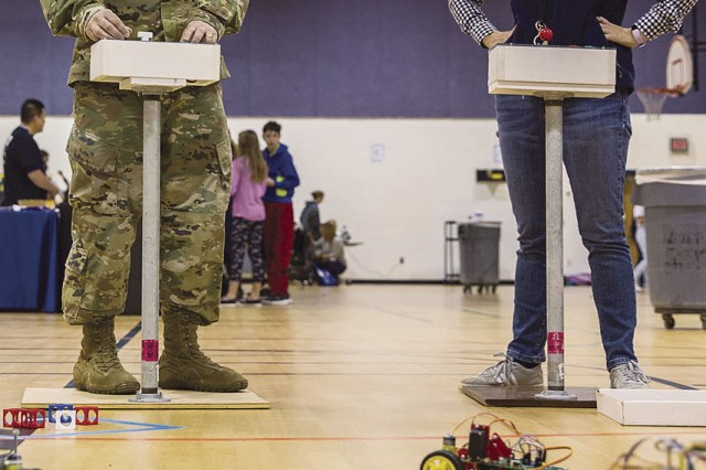 Col. Michael Greenberg, Garrison commander, maneuvers a robot, while Margo Pareja, Fort Belvoir Primary School principal, looks on during Family STEAM Day, Nov. 16.