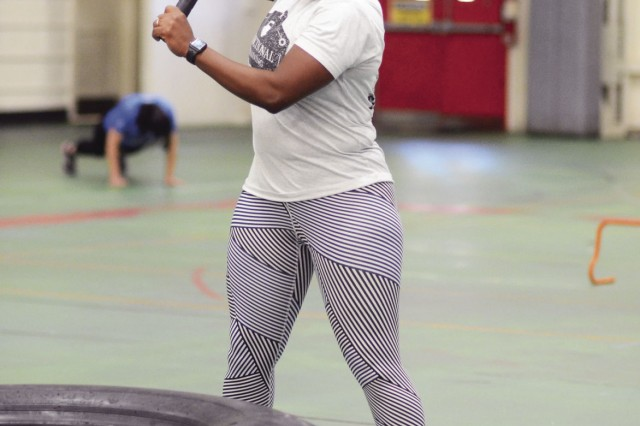 Maj. Pamela Rainey, OCAR, builds core strength at the sledgehammer station during a midday Functional Fitness workout, Nov. 13 at Specker Field House.
