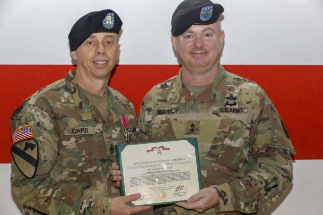 U.S. Army Maj. Gen. Christopher Mohan, 21st Theater Sustainment Command commanding general, presents the Legion of Merit award to U.S. Army Command Sgt. Maj. Rocky Carr, outgoing 21st Theater Sustainment Command senior enlisted advisor, as part of a change of responsibility ceremony in Sembach, Germany, Nov. 21, 2019. The Legion of Merit is an award that is given for exceptionally meritorious conduct in the performance of outstanding services and achievements and is the seventh in the order of precedence of all U.S. military awards. (U.S. Army photo by Spc. Elliott Page)