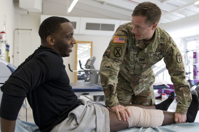 Capt. Daniel Huffman, physical therapist and assistant chief of Rehabilitation Services at Landstuhl Regional Medical Center, assists Spc. Andrew Barrett, culinary specialist, 55th Quartermaster Company, Special Troops Battalion, 16th Sustainment Brigade, 21st Theater Sustainment Command, with stretches as part of Barrett's rehabilitation plan at LRMC's Rehabilitation Clinic, Nov. 21. A team of rehabilitation specialists, including Huffman, recently participated in a Global Health Engagement medical exercise at with Ukrainian counterparts at a military hospital in Lviv, Ukraine, to build relationships and strengthen global health initiatives with partner nations and allies.