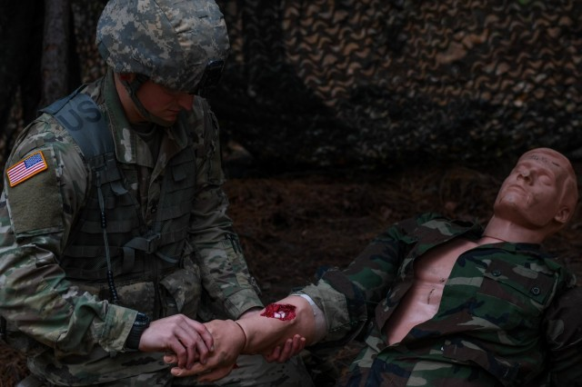 U.S. Army Staff Sgt. Edward Chase, a drill sergeant with the 2-39 Infantry Battalion, 165th Inf. Brigade at Fort Jackson, examines a wound during the medical lane of the Expert Soldier Badge course at Joint Base Langley-Eustis, Va., Nov. 18, 2019. There were 10 tasks in the medical lane, including requesting medical evacuation, providing care under fire, moving a casualty and controlling blood loss.