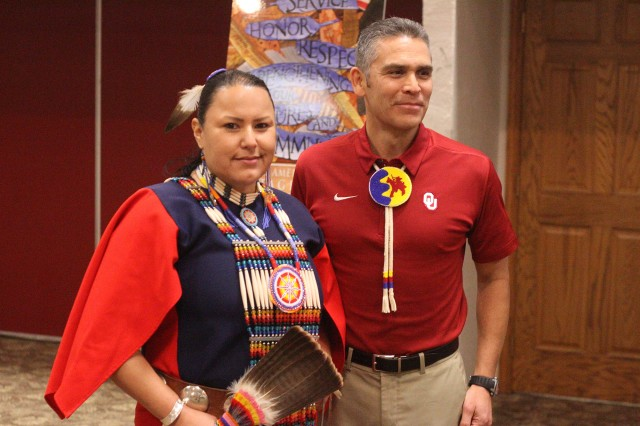 """Marla Nauni, a Comanche recording artist, actress, and model, wears her blue and red battle dress with accessories made by her ancestors. She sang """"The Comanche Blessing Song"""" at the National American Indian Heritage Month luncheon at Fort Sill, Oklahoma. With her is her cousin, retired Lt. Col. Mark Woommavovah, who was the guest speaker for the Nov. 21, 2019, event."""