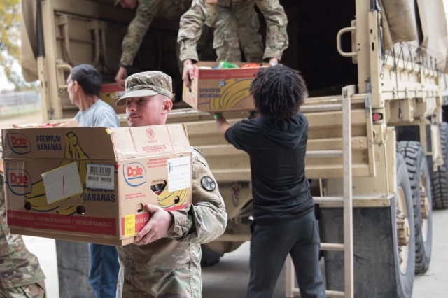 Shreveport, Louisiana native Cpl. Mike Schreckengost, 61st Quartermaster Battalion, unloads donations to be weighed and sorted Nov. 22.  Soldiers from 61st Quartermaster Battalion, units across Fort Hood and community supporters from the Killeen area supported the 30th annual Food for Families food drive at the Killeen Special Events Center.