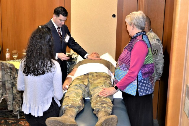"""Mr. Robert Dennis, Director of the Clinical Nurse Transition Program, Landstuhl Regional Medical Center, counts respirations for a full minute to highlight the benefits and cost savings of using a """"Live Actor"""" during a simulation."""