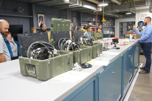 Craig Hoffman, Letterkenny Munitions Center, speaks to the Singapore Armed Forces Ammunition Command about the process of the W1 Cable Modification at the Missile Test Set repair operations.