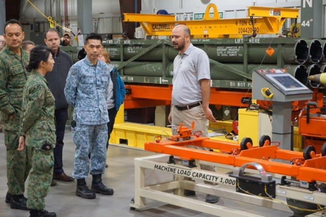 Travis Moore, Letterkenny Munitions Center, speaks to the Singapore Armed Forces Ammunition Command about the Multiple Launch Rocket System download process for reclaiming components to support the production of  Low Cost Reduced Range Practice Rocket Motor
