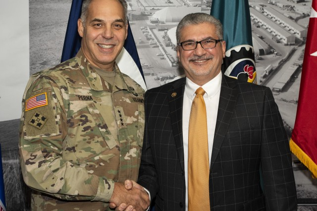 Gen. Gus Perna, commanding general, U.S. Army Materiel Command, congratulates Gil Ponce, Africa Command and European Command branch chief, Logistics Civil Augmentation Program Operations, after presenting his AMC four-star coin and AMC lapel pin Nov. 19 prior to the U.S. Army Sustainment Command Quarterly Update. (Photo by Linda Lambiotte, ASC Public Affairs)