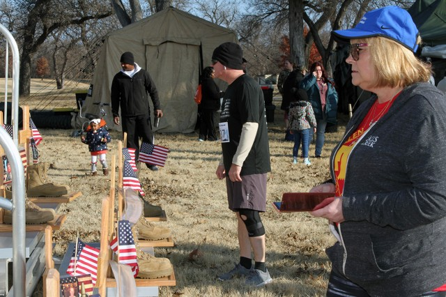 Runners and families look over a memorial of local fallen service members which was featured at the Run for the Fallen Nov. 23, 2019. The display was created by the Fort Sill Survivor Outreach Services.