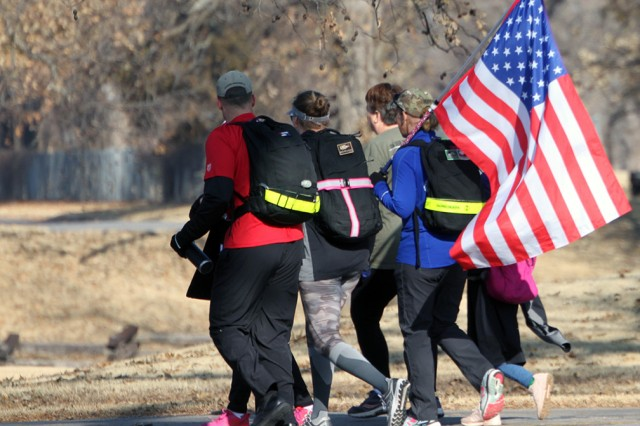 A family carries a U.S. flag as they walk during the Run for the Fallen 5K Nov. 23, 2019. The route took them around the Fort Sill Golf Course and back to the start/finish at the Patriot Club.
