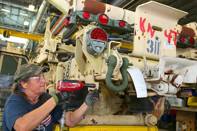 A Red River Army Depot, Texas employee repairs a truck inside the depot's maintenance facility.