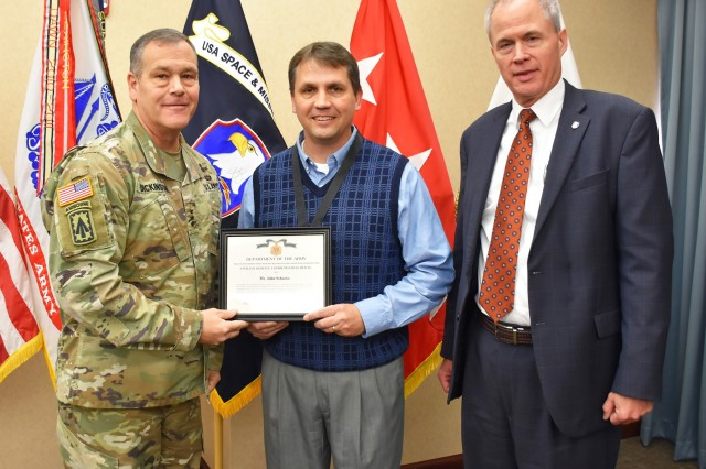 Lt. Gen. James H. Dickinson, commanding general, U.S. Army Space and Missile Defense Command, presents John C. Schocke, USASMDC headquarters deputy chief of staff, for the technical/technical management category, with the command's 2019 Civilians of the Year for technical/technical management category award during a ceremony Nov. 20 at the command's Redstone Arsenal, Alabama, headquarters. (U.S. Army photo by Ronald Bailey)